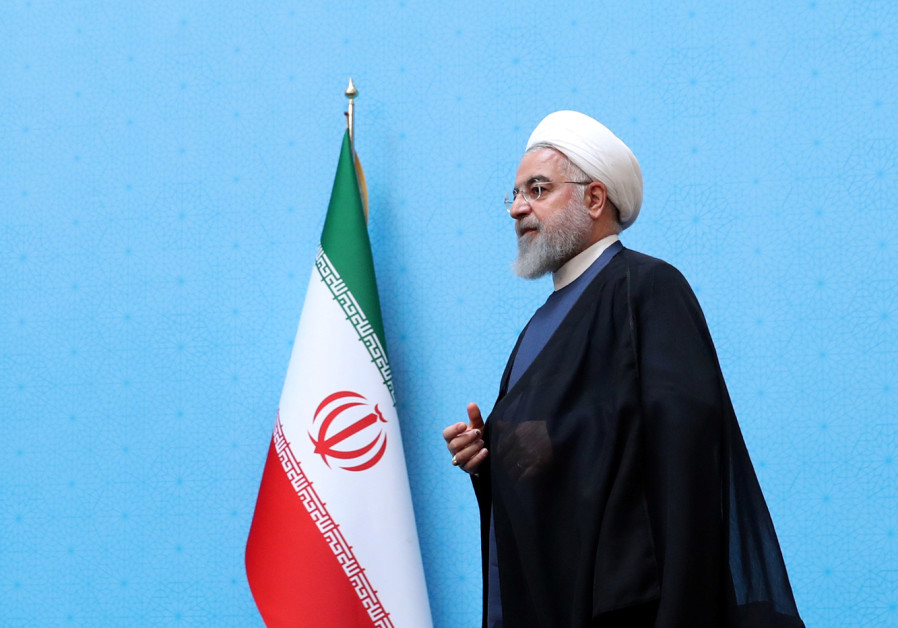 Iranian President Hassan Rouhani walks to deliver a speech during the Conference of Government's Ach