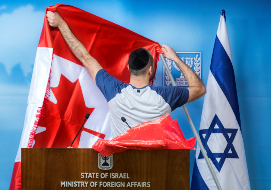 An employee adjusts the Canadian flag next to the Israeli one
