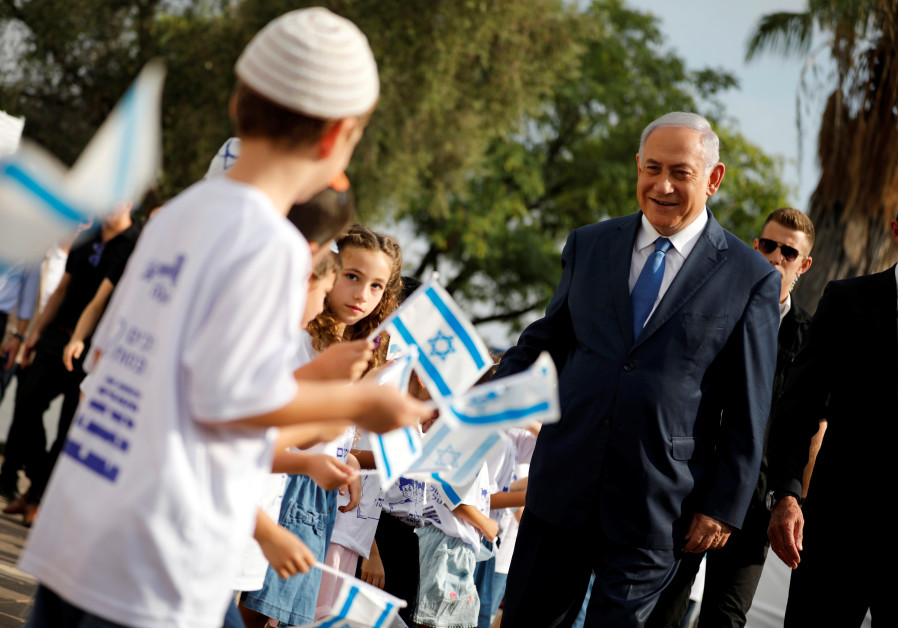 Israeli Prime Minister Benjamin Netanyahu greets students as they wave Israeli flags during a ceremo