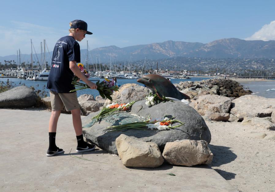 Colin Martz, 16, an intern at the Santa Barbara Sailing Center, walks to place flowers at a memorial