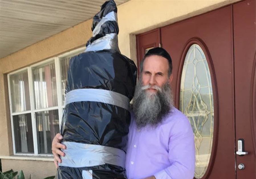 Rabbi Zvi Konikov with one of three Torah scrolls being transported off Satellite Beach, the barrier