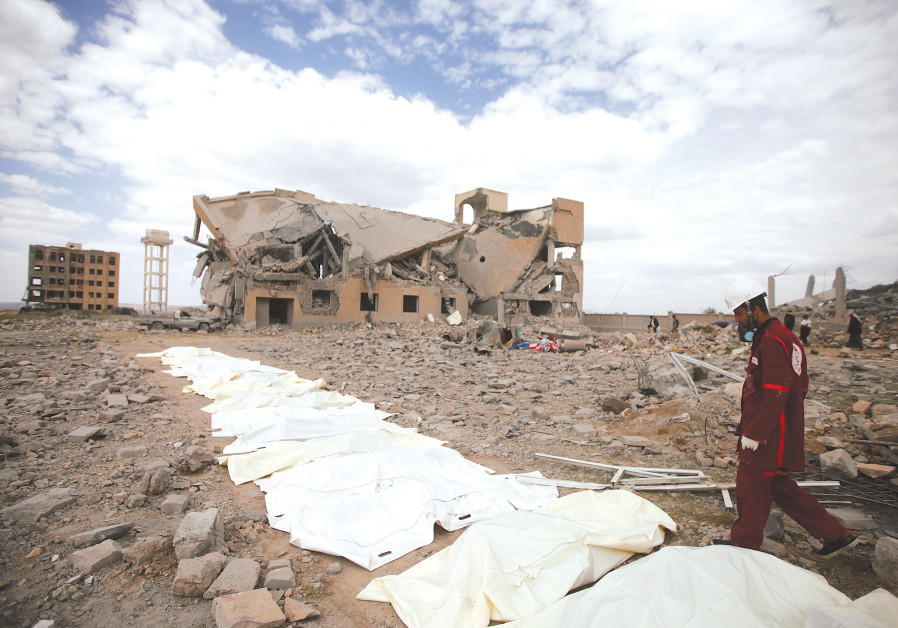 A RED CRESCENT medic walks next to bags containing the bodies of victims of Saudi-led airstrikes on