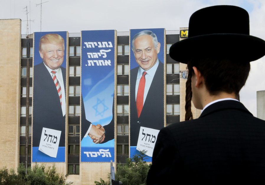 A haredi man stares at a Likud ad with Prime Minister Benjamin Netanyahu and President Donald Trump.