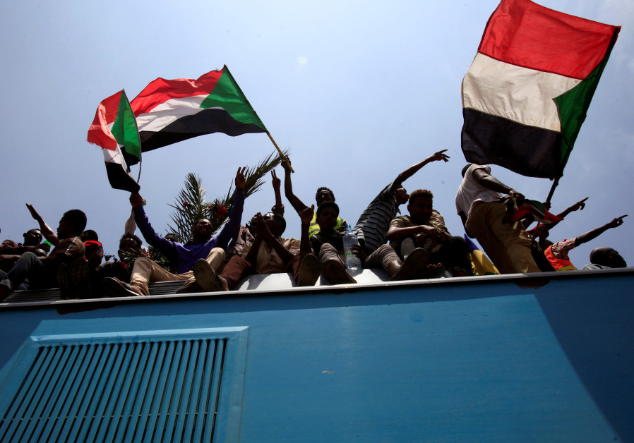 Sudanese civilians wave their national flags during the signing of the Sudan's power sharing deal