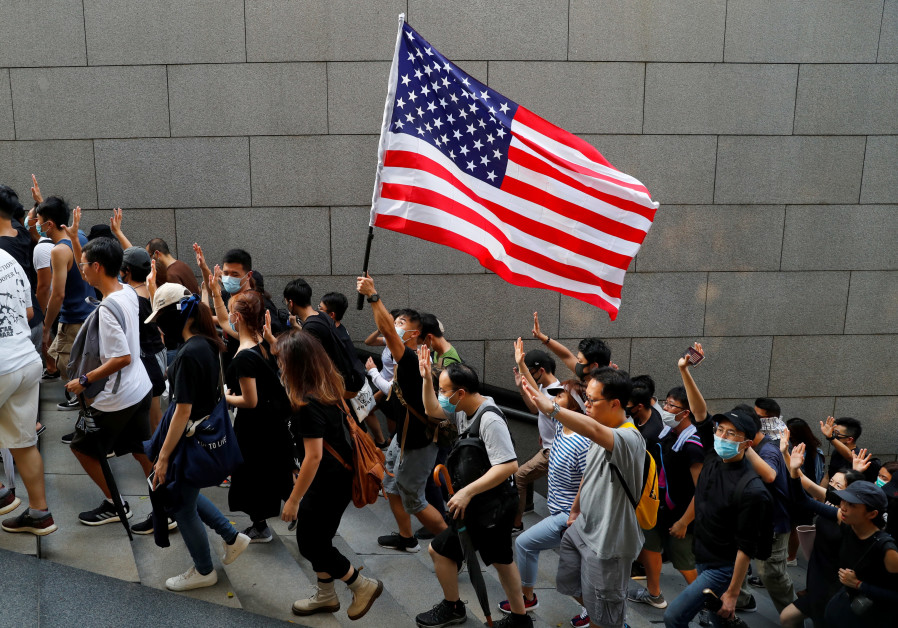 Protesters hold up five fingers and a U.S. flag during a rally to the U.S. Consulate General in Hong