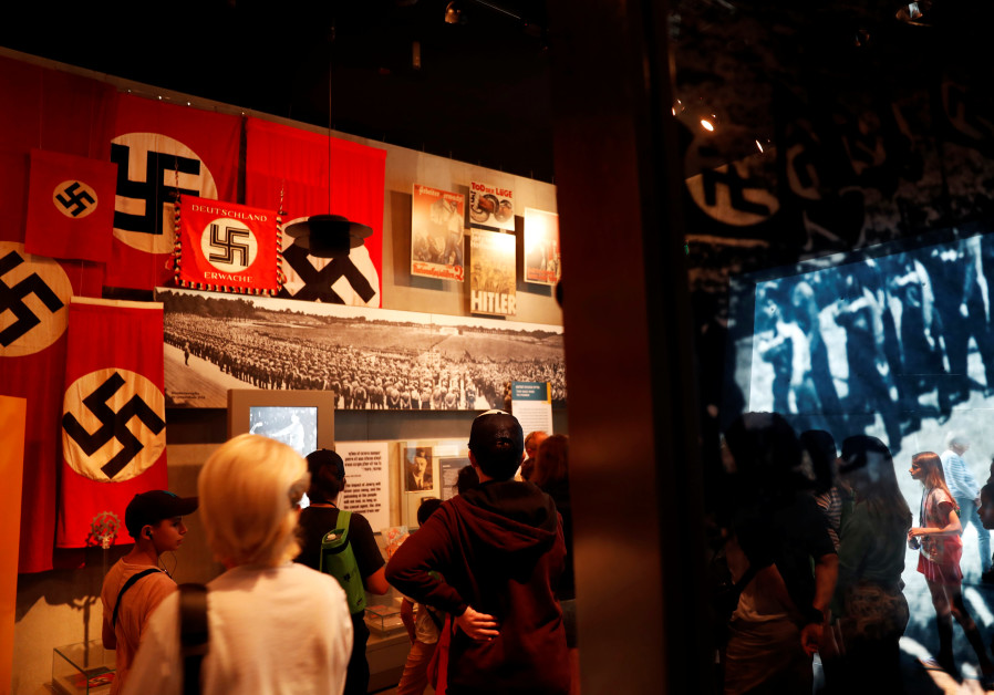 Visitors at an exhibition, look at Nazi flags and banners bearing Swastikas, at Yad Vashem World Hol