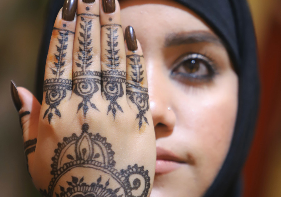 An Iraqi woman holds up her hand decorated with henna inside her beauty shop in Basra