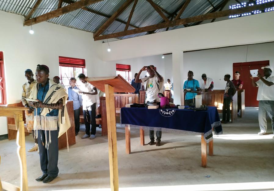Members of the Mukono Jewish community read from the Torah.