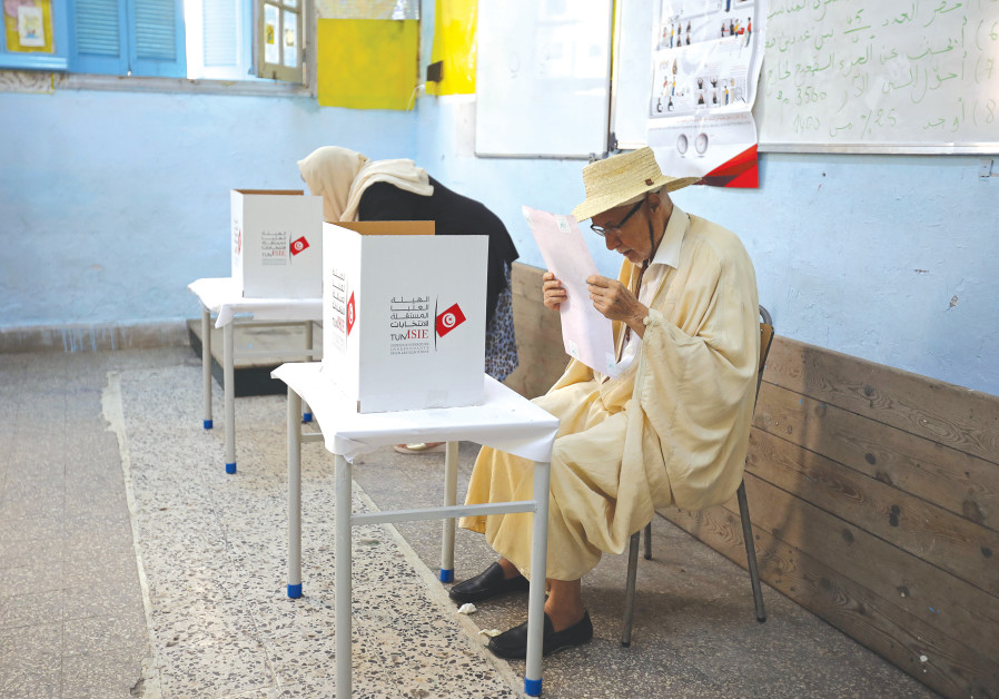 A MAN READS his ballot paper at a polling station during the presidential election in Tunis yesterda