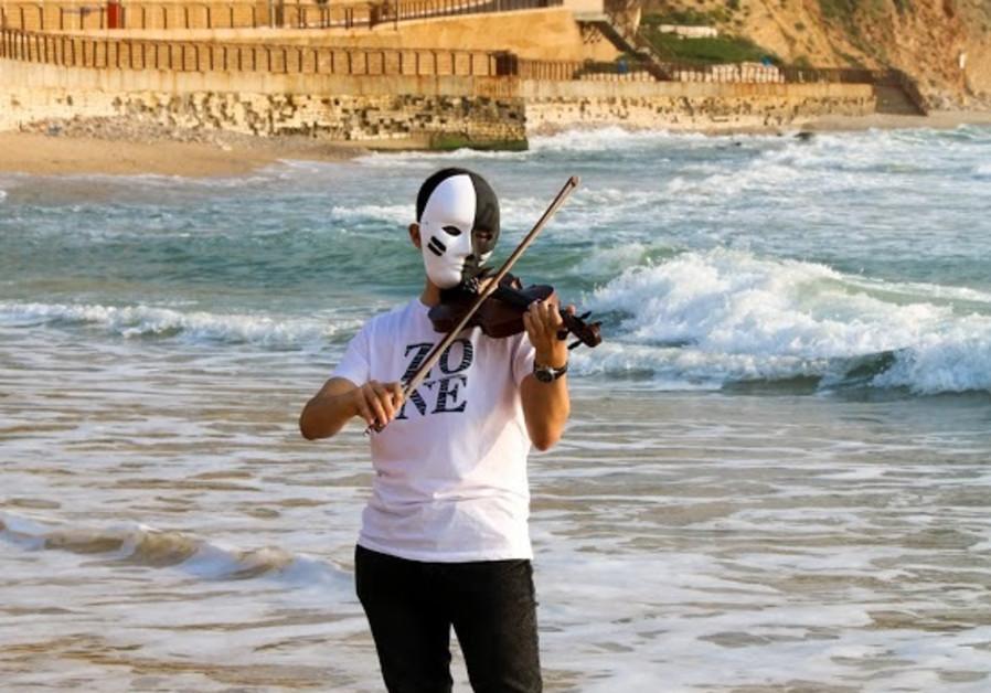 Violinist at Netanya beach playing Arabic music (Courtesy Givat Haviva).