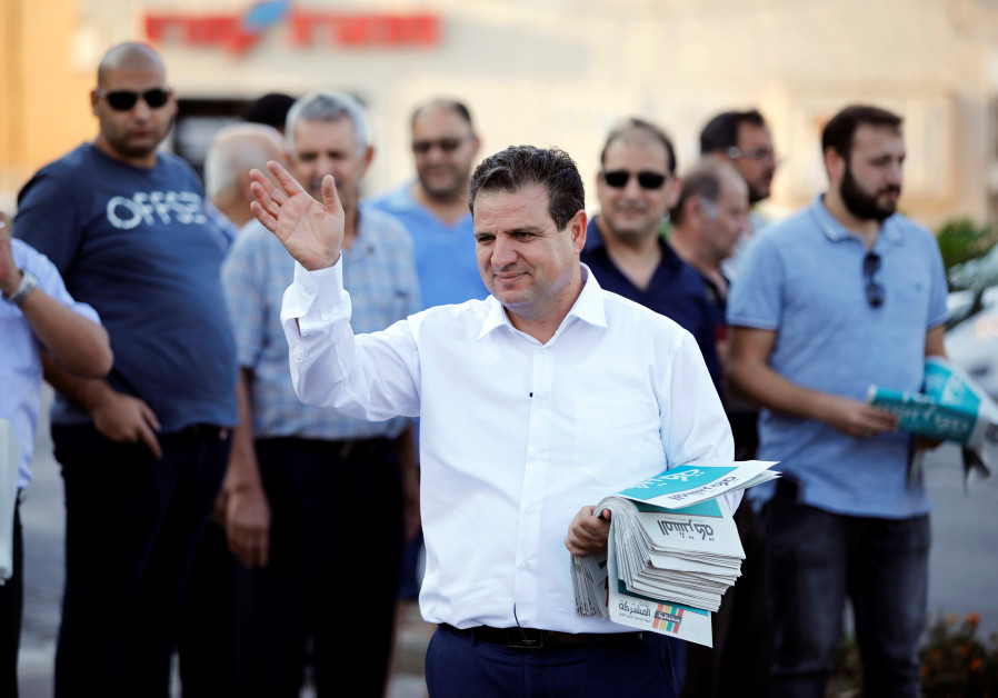 Ayman Odeh, leader of the Joint List, gestures as he hands out pamphlets during an election campaign