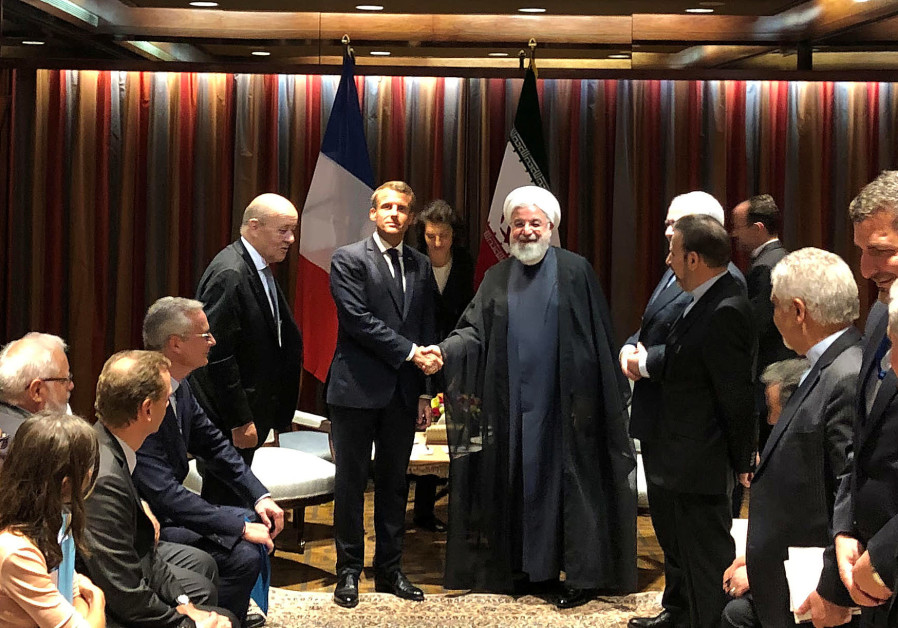 French President Emmanuel Macron shakes hands with Iranian President Hassan Rouhani during their mee