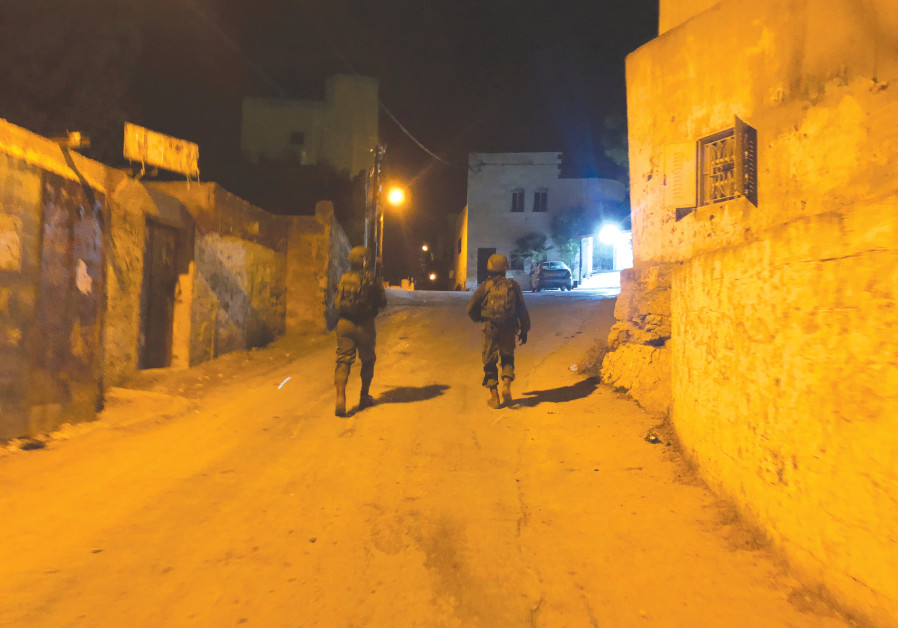 ON PATROL in the village of Kafr Nima. 'Everyone has their time. Don't worry, we will find them.'