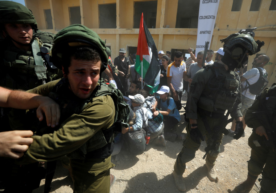 Israeli soldiers detain local and foreign activists during a protest against Jewish settlements, nea