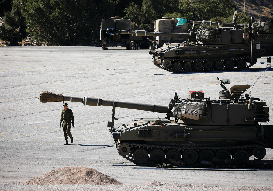 A SOLDIER walks next to a tank on the Golan