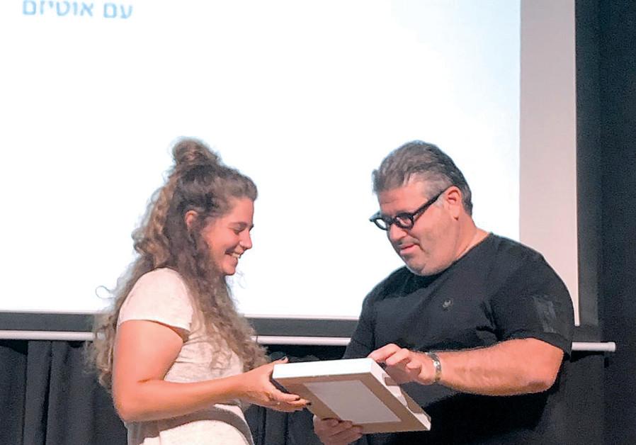 RAN RAHAV presents a citation and check to Hodaya Dekel of Alut.
