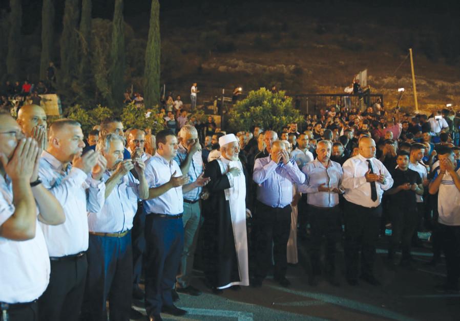 Ayman Odeh (C) prays at the funeral of the brothers killed this week in Majd el-Kurum.