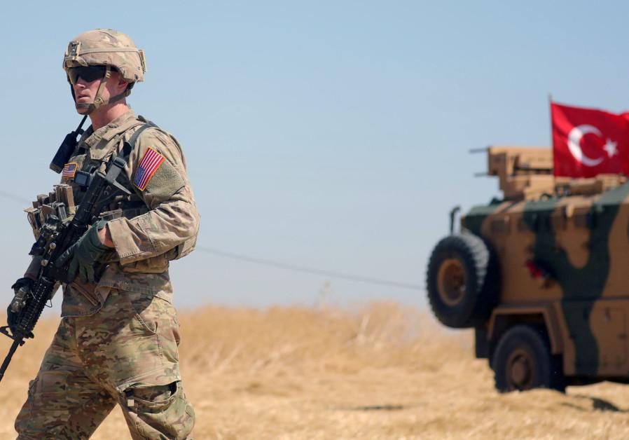 An American soldier walks near a Turkish military vehicle during a joint U.S.-Turkey patrol, near Te