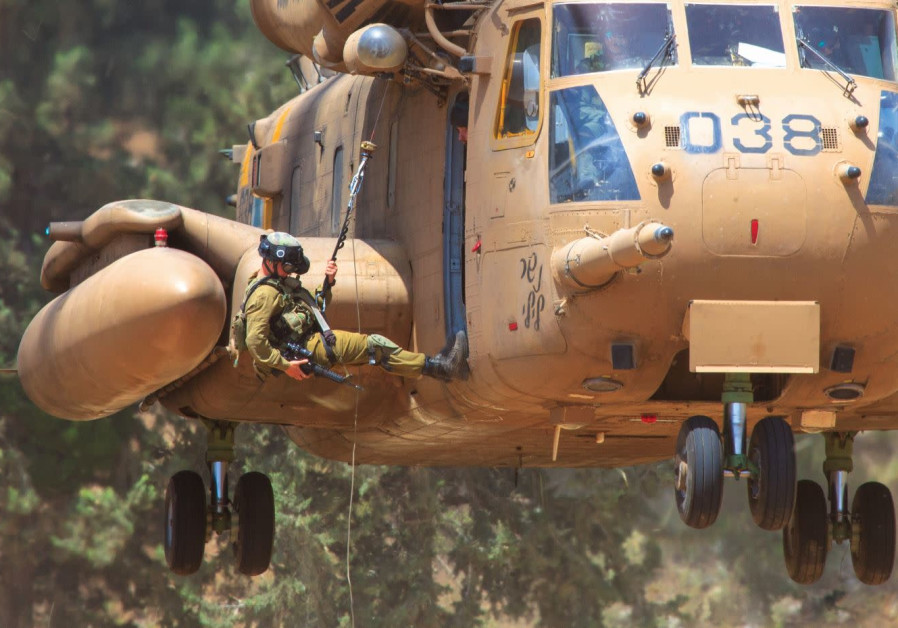 A UNIT 669 soldier uses a rope to descend from a helicopter during a training exercise