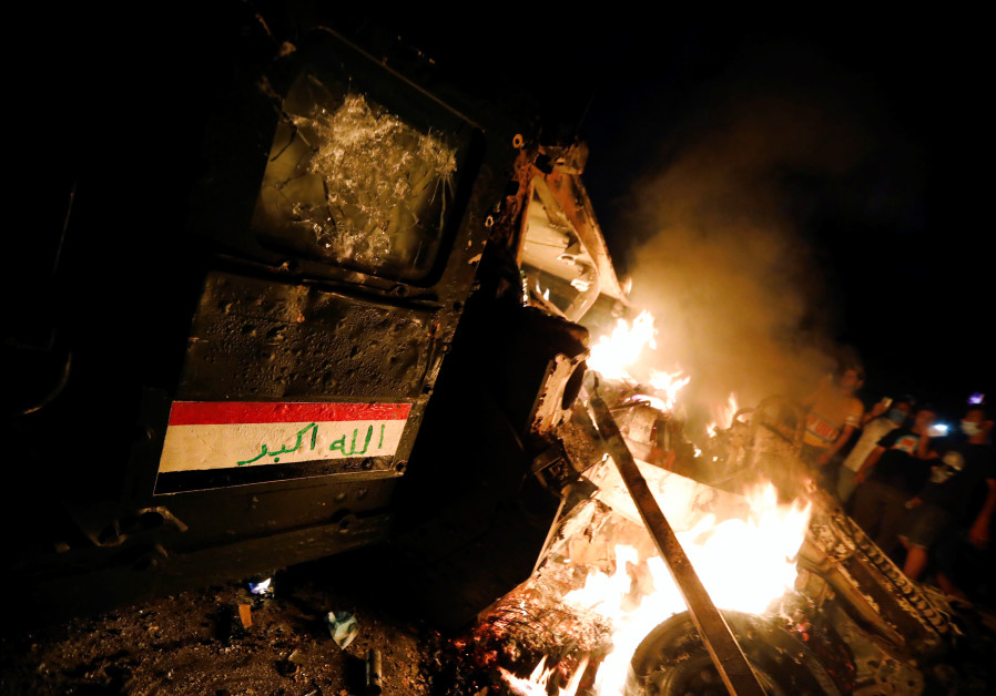 Protesters burn an armoured vehicle belonging to Iraqi rapid response force at a protest in Baghdad
