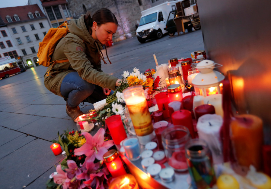 People place candles at central market square in Halle, Germany October 10, 2019, after two people w