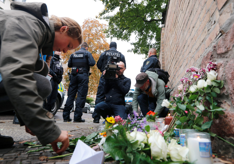 People lay flowers outside the synagogue in Halle, Germany October 10, 2019, after two people were k