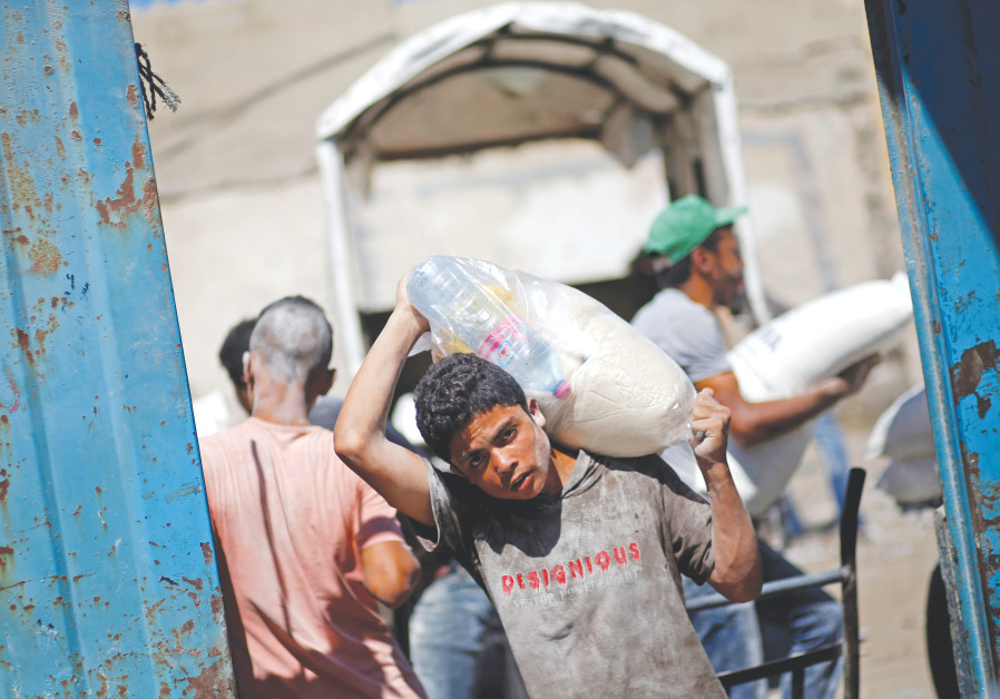 A PALESTINIAN carries food supplies at a Gaza aid distribution center run by the United Nations Reli