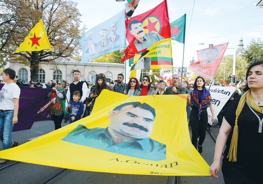 KURDISH PROTESTERS carry flags and a banner with a portrait of jailed Kurdistan Workers Party (PKK)