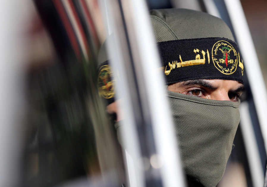 A Palestinian Islamic Jihad militant looks out of a vehicle during a military show marking the 32nd