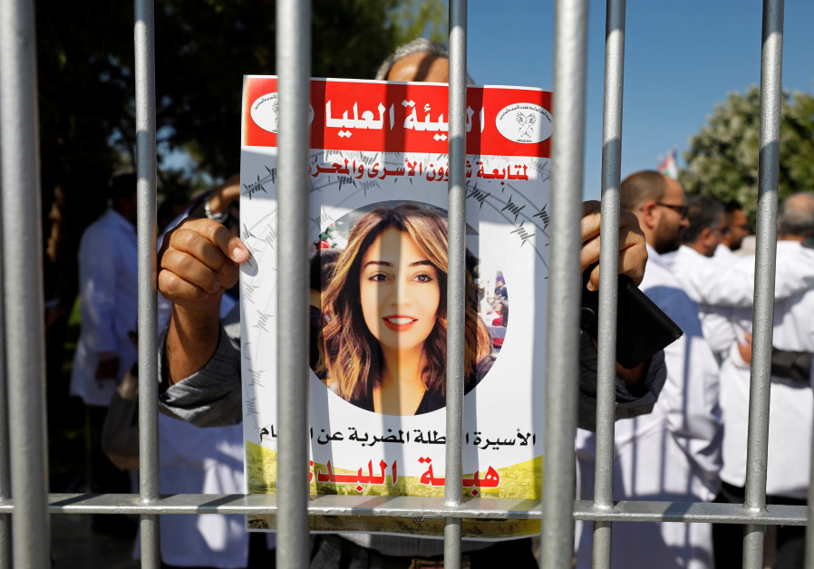 A demonstrator holds a picture of Jordanian citizen Hiba Labadi during a protest calling for the rel