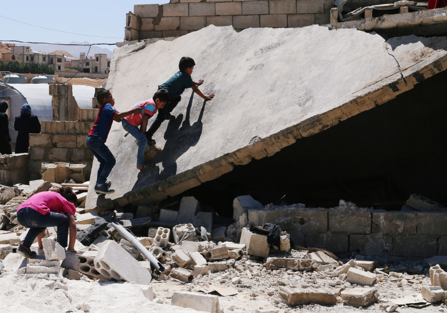 Syrian refugee kids play on a rubble of dismantled concrete huts at a makeshift Syrian refugee camp
