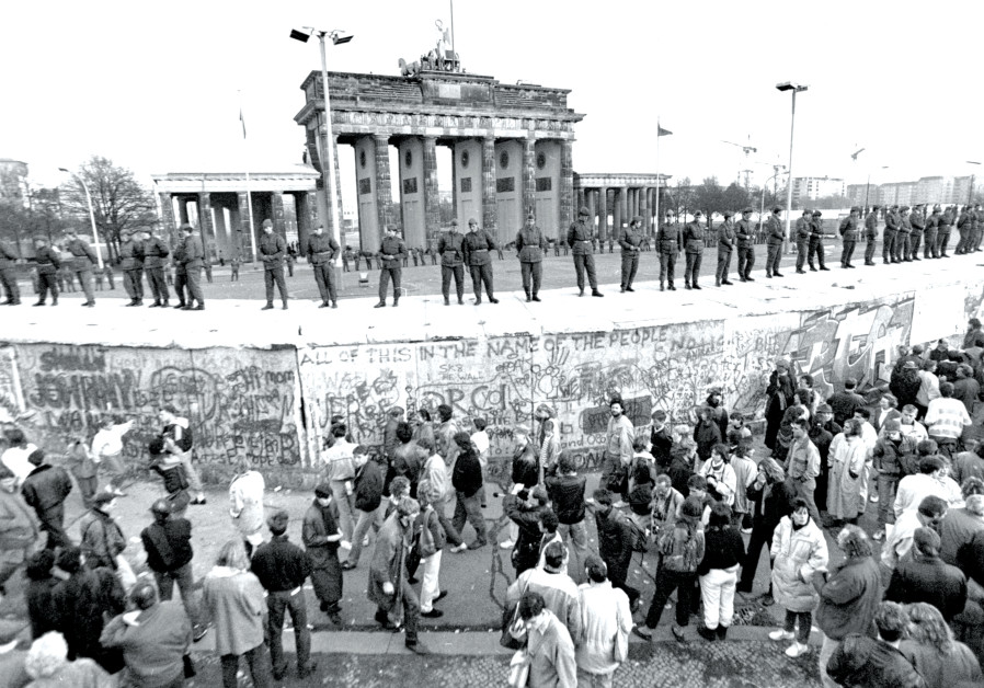 SOLDIERS STAND at ease on top of the Berlin Wall, in front of Brandenburg Gate, on November 10, 1989
