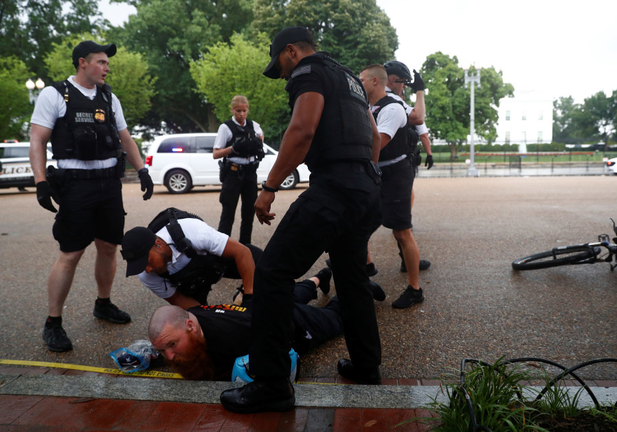U.S. Secret Service Uniformed Division officers detain a man in front of the White House during a Fo
