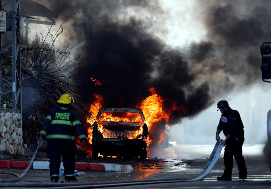 Les pompiers éteignent un véhicule qui brûle après l'incendie d'une usine à Sderot