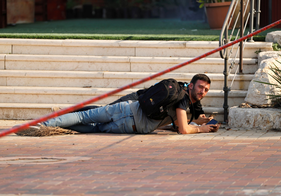 An Israeli man seeks cover during a missile attack in Sderot. (Reuters)