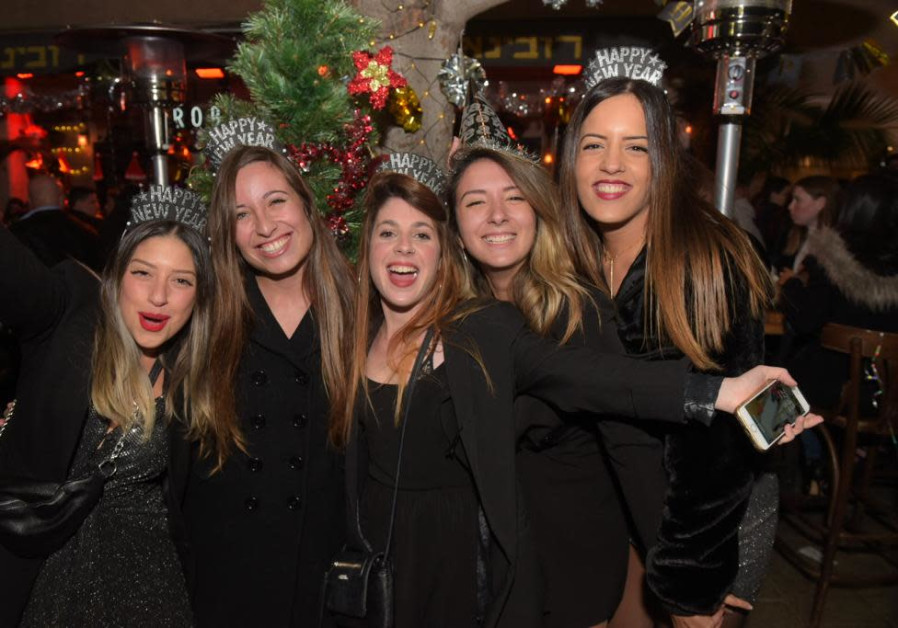 A group of friends wear matching crowns as they welcome New Year 2020. (AVSHALOM SASSONI/MAARIV)