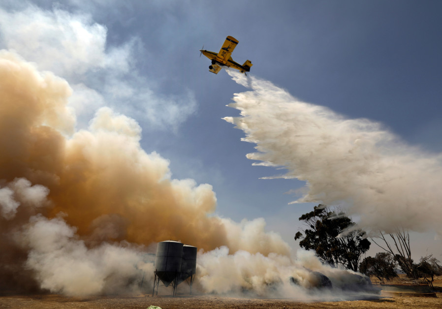 On Kangaroo Island, a pilot drops water on a a fire on Jan. 13, 2020. The bushfires on Kangaroo Island have been devastating for farmers, many of whom have lost sheep and grazing land for their animals. (photo credit: CAROLYN COLE/LOS ANGELES TIMES/TNS)