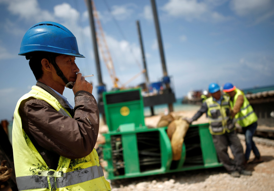 Chinese construction workers work during a media tour of the construction of a new port in the southern city of Ashdod, Israel April 12, 2016. The new port in Ashdod together with another one in Haifa are both under construction and are planned to start operating at the end of 2021. (Credit: Reuters)