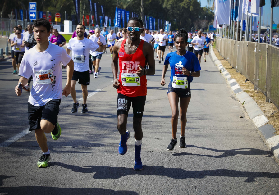 Ethiopian-born Gezachew Fanta (left) running the 2020 Tel Aviv Marathon in honor of the FIDF IMPACT! Scholarship Program with his wife (right).  (Credit: Guy Yechiely)