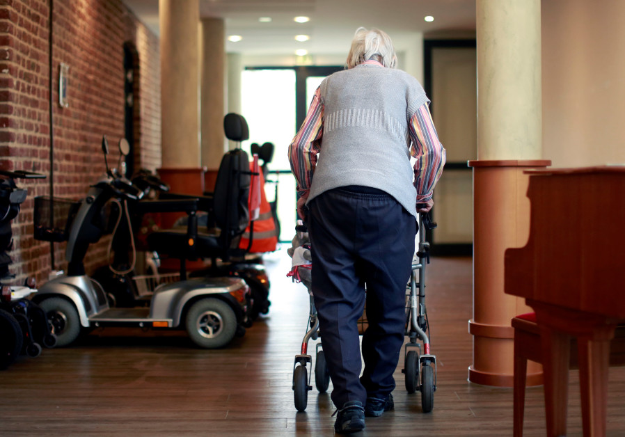 An elderly woman walks through a corridor of a retirement home as visits have been restricted due to the coronavirus disease (COVID-19) concerns, in Grevenbroich (REUTERS)