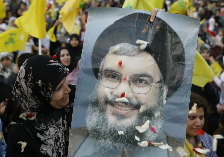 A HEZBOLLAH supporter beams at a poster of Hezbollah leader Hassan Nasrallah during a rally on the anniversary of the Israeli withdrawal, on May 25, 2009. (Jamal Saidi/Reuters)