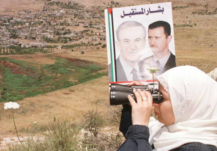 A SYRIAN woman from the Golan Heights village of Ain al-Tinaeh holds a poster of deceased Syrian president Hafez Assad and son Bashar as she searches for relatives in the village of Majdal Shams, across the border in Israel, in July 2000. (Kh.H/Reuters)