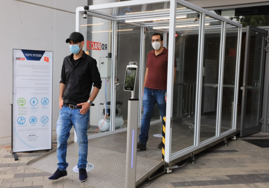 Bar-Ilan University researchers Dr. Eran Avraham (front) and Dr. Izaak Cohen (back) walk through a disinfection tunnel at Bloomfield Stadium (Credit: Yoni Reif)