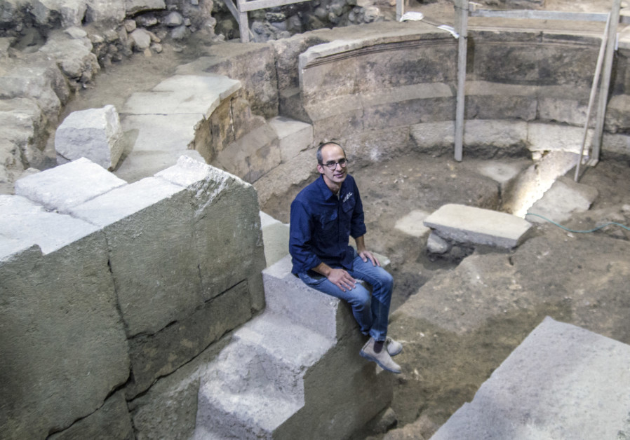 Dr. Joe Uziel of the Israel Antiquities Authority sits on the steps of the theater-shaped building uncovered by the Western Wall in Jerusalem. (Credit: Yaniv Berman, Courtesy of the Israel Antiquities Authority)
