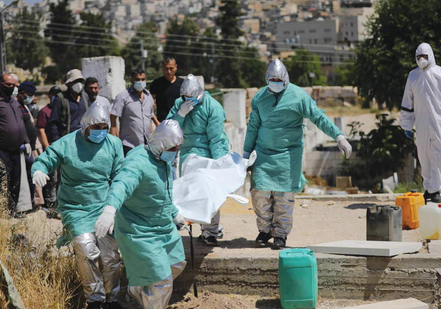 SUITED UP at a funeral for a COVID-19 victim in Hebron this month (Photo Credit: Noor Khatib)