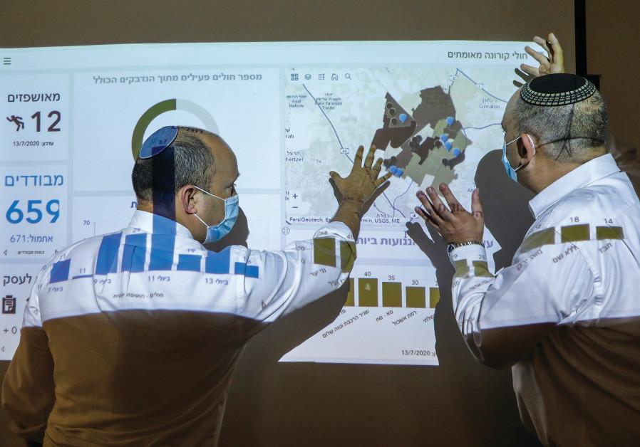 Naftali Bennett examines data on local coronavirus infections in Lod. (Marc Israel Sellem / Jerusalem Post)