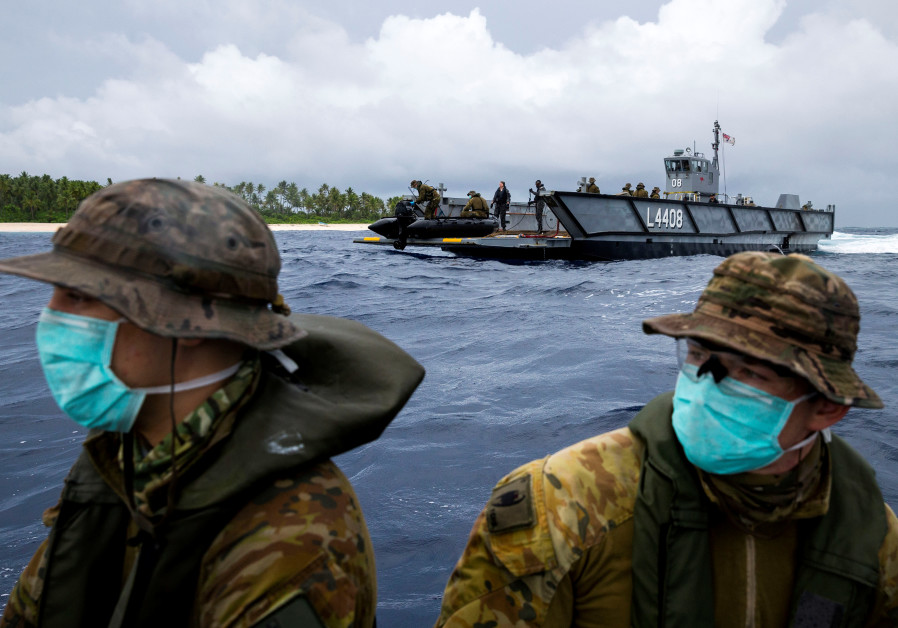 Australian Army soldiers launch a zodiac inflatable boat from one of HMAS Canberra's Landing Craft to deliver food and supplies to three stranded mariners following a search and rescue mission, on Pikelot Island, Micronesia August 3, 2020. (photo credit: AUSTRALIAN DEPARTMENT OF DEFENCE/REUTERS)