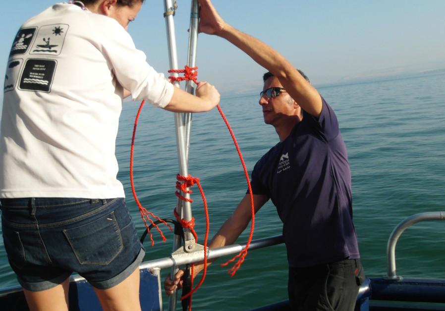 Naama Sarid and Michael Lazar installing the sonar on the boat in the Sea of Galilee. (Naama Sarid)