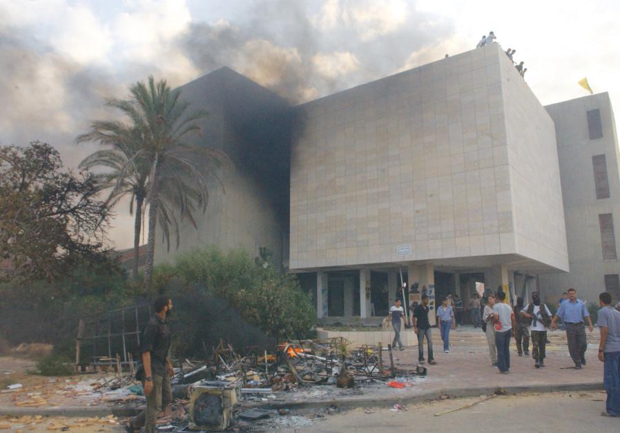 Palestinians burn the yeshiva in evacuated Neveh Dekalim on September 13, 2005. (Yossi Zamir/Flash90)