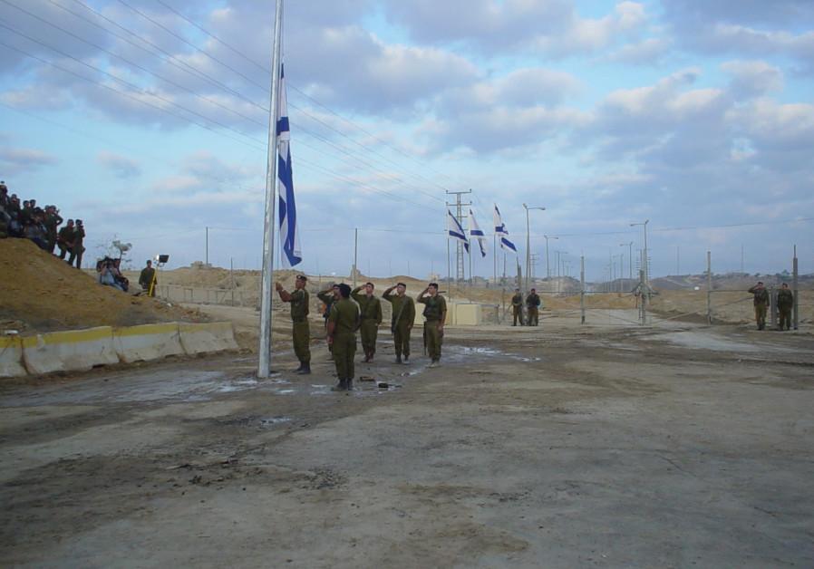 THE IDF locks the gate and lowers the flag at dawn on September 12, 2005, as IDF Gaza Division commander Brig.-Gen. Aviv Kochavi salutes. (Credit: Arieh O'Sullivan)
